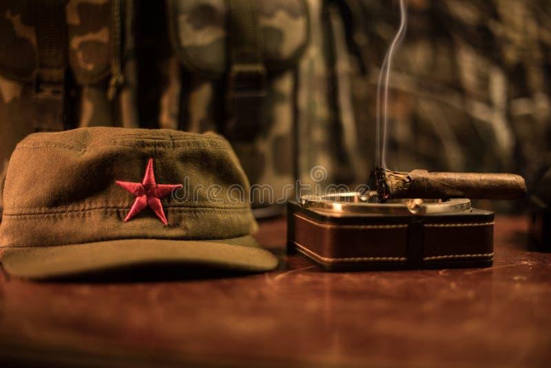 Κλείστε επάνω ενός κουβανικά πούρου και ashtray στον ξύλινο πίνακα Κομμουνιστικός πίνακας διοικητών δικτατόρων στο σκοτεινό δωμάτ στοκ εικόνα με δικαίωμα ελεύθερης χρήσης