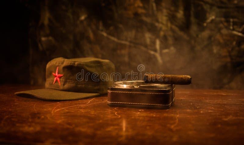 Κλείστε επάνω ενός κουβανικά πούρου και ashtray στον ξύλινο πίνακα Κομμουνιστικός πίνακας διοικητών δικτατόρων στο σκοτεινό δωμάτ στοκ φωτογραφίες
