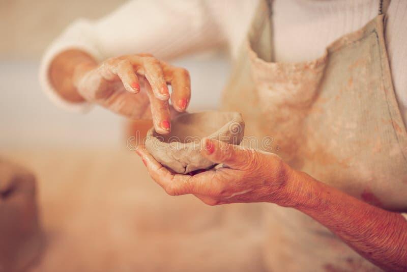 Κλείστε επάνω ενός κύπελλου αργίλου στα θηλυκά χέρια στοκ φωτογραφία