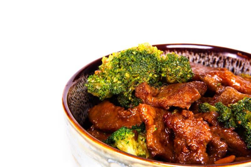 Κλείστε επάνω ενός κύπελλου των κινεζικών τροφίμων, του βόειου κρέατος και του μπρόκολου ανακατώνω-τηγανητών σε ένα άσπρο υπόβαθρ στοκ φωτογραφίες