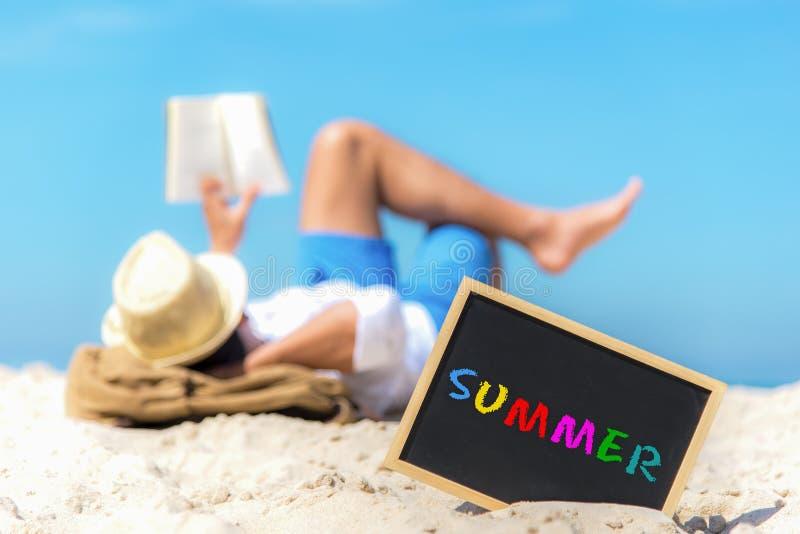 Κλείστε επάνω ενός πίνακα κιμωλίας με το καλοκαίρι κειμένων που γράφεται σε το στην άμμο μιας παραλίας, στοκ εικόνα