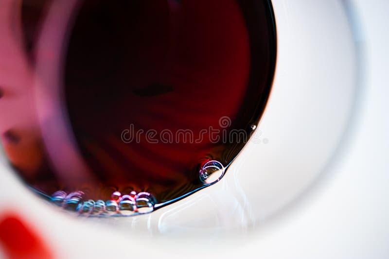 Κλείστε επάνω ενός ποτηριού του κόκκινου κρασιού με τις μικρές φυσαλίδες στην άκρη στοκ εικόνες