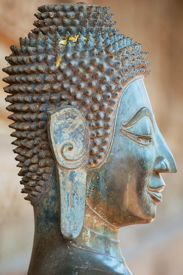 Κλείστε επάνω ενός προσώπου ενός αρχαίου αγάλματος του Βούδα χαλκού έξω από το ναό Hor Phra Keo σε Vientiane, Λάος στοκ φωτογραφίες