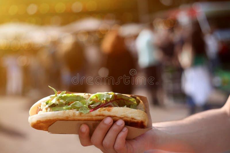 Κλείστε επάνω ενός χοτ-ντογκ υπό εξέταση ενάντια στο θολωμένο φεστιβάλ τροφίμων θερινών οδών στοκ φωτογραφία με δικαίωμα ελεύθερης χρήσης