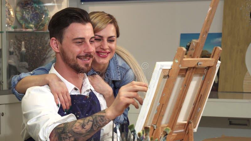 Κλείστε επάνω ενός όμορφου σχεδίου καλλιτεχνών στο στούντιό του ενώ η σύζυγός του που αγκαλιάζει τον στοκ φωτογραφία με δικαίωμα ελεύθερης χρήσης