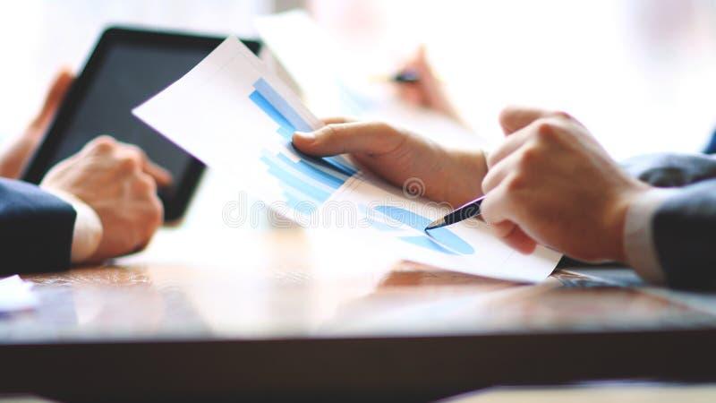 κλείστε επάνω επιχειρηματίας και βοηθός που ελέγχουν την οικονομική έκθεση στοκ εικόνα