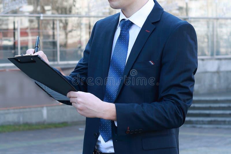 κλείστε επάνω επιχειρηματίας που κάνει τις σημειώσεις για την περιοχή αποκομμάτων στοκ φωτογραφία