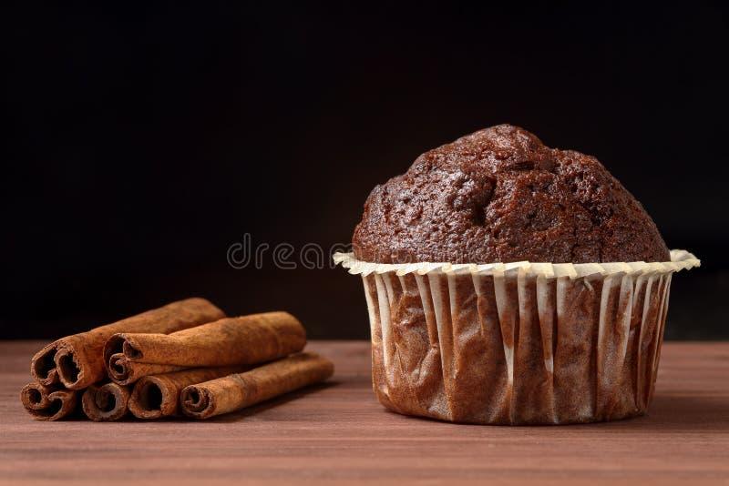Κλείστε επάνω εύγευστο muffin σοκολάτας με τα ραβδιά κανέλας σε έναν ξύλινο πίνακα στο μαύρο κλίμα Διάστημα για το κείμενο στοκ φωτογραφίες με δικαίωμα ελεύθερης χρήσης