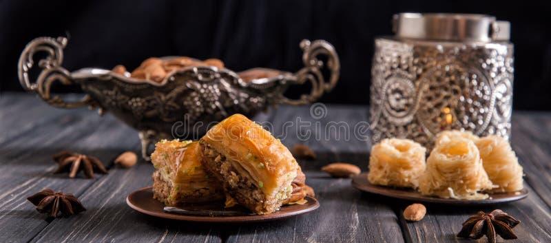 κλείστε επάνω 1 ζωή ακόμα Τούρκος γλυκών μπισκότων Παραδοσιακό baklava μελιού, καρύδια Αγγειοπλαστική και ασημικές σκοτεινός ξύλι στοκ φωτογραφία