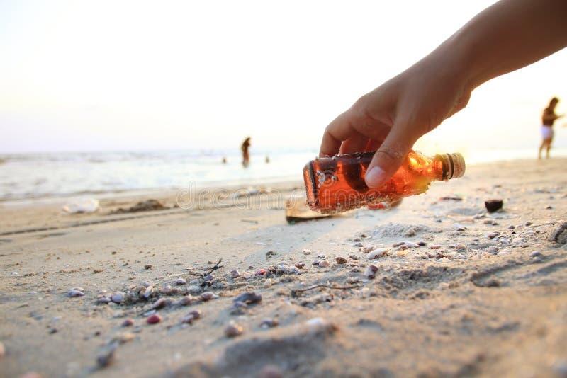 Κλείστε επάνω μαζεύει με το χέρι το μπουκάλι γυαλιού στην παραλία στοκ εικόνες