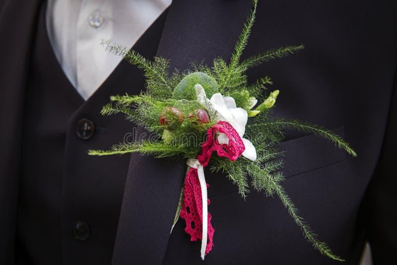 Κλείστε επάνω μιας γαμήλιας μπουτονιέρας στο κοστούμι γαμπρών Το στήθος νεόνυμφων με τους πράσινους κλαδίσκους και τα κόκκινα μού στοκ φωτογραφίες
