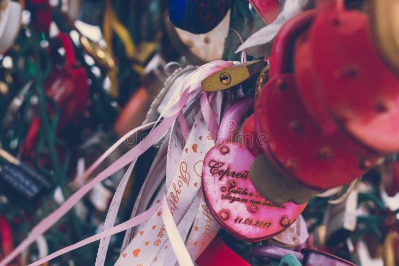 Κλείστε επάνω μιας κλειδαριάς αγάπης σε ένα κιγκλίδωμα σε μια γέφυρα κλειδαριών με άλλες κλειδαριές που θολώνονται για να δημιουρ στοκ φωτογραφίες