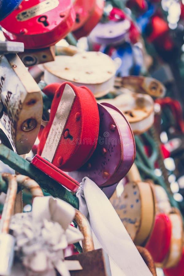 Κλείστε επάνω μιας κλειδαριάς αγάπης σε ένα κιγκλίδωμα σε μια γέφυρα κλειδαριών με άλλες κλειδαριές που θολώνονται για να δημιουρ στοκ εικόνες με δικαίωμα ελεύθερης χρήσης