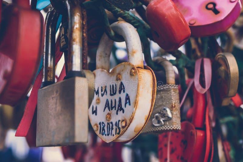 Κλείστε επάνω μιας κλειδαριάς αγάπης σε ένα κιγκλίδωμα σε μια γέφυρα κλειδαριών με άλλες κλειδαριές που θολώνονται για να δημιουρ στοκ φωτογραφία με δικαίωμα ελεύθερης χρήσης