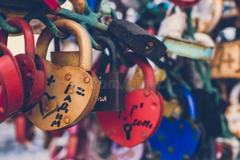 Κλείστε επάνω μιας κλειδαριάς αγάπης σε ένα κιγκλίδωμα σε μια γέφυρα κλειδαριών με άλλες κλειδαριές που θολώνονται για να δημιουρ στοκ φωτογραφίες με δικαίωμα ελεύθερης χρήσης