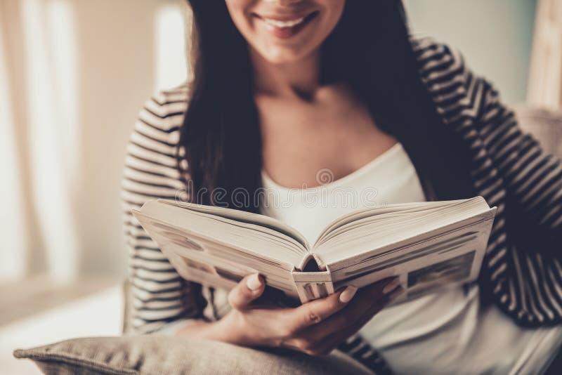 κλείστε επάνω Νέο βιβλίο ανάγνωσης γυναικών χαμόγελου στο σπίτι στοκ φωτογραφία