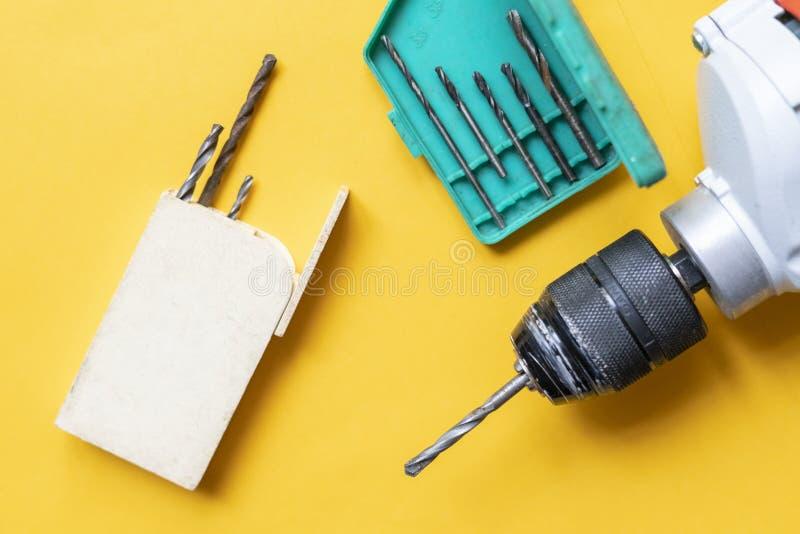 Κλείστε επάνω να μαζεψει με το χέρι ένα εργαλείο επισκευής τρυπανιών στο κίτρινο υπόβαθρο φ στοκ φωτογραφίες με δικαίωμα ελεύθερης χρήσης