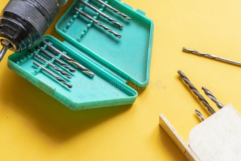 Κλείστε επάνω να μαζεψει με το χέρι ένα εργαλείο επισκευής τρυπανιών που απομονώνεται στο κίτρινο υπόβαθρο φ στοκ εικόνες