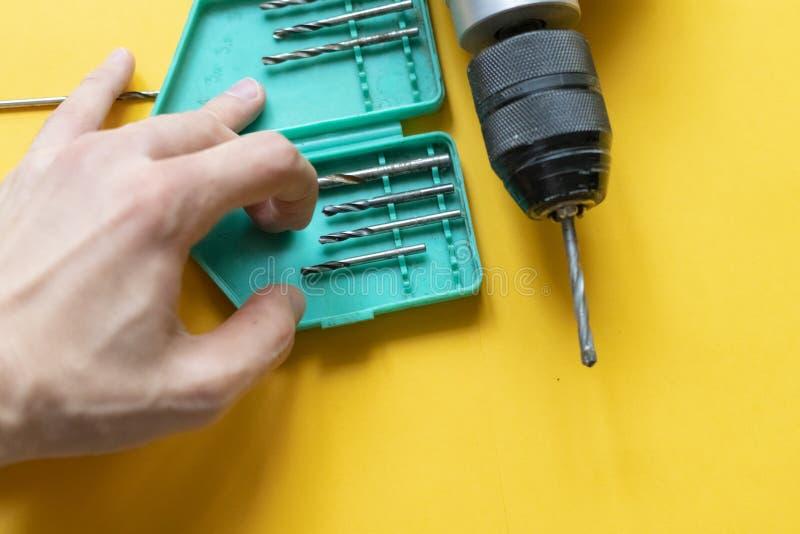 Κλείστε επάνω να μαζεψει με το χέρι ένα εργαλείο επισκευής τρυπανιών που απομονώνεται στο κίτρινο υπόβαθρο φ στοκ φωτογραφία με δικαίωμα ελεύθερης χρήσης