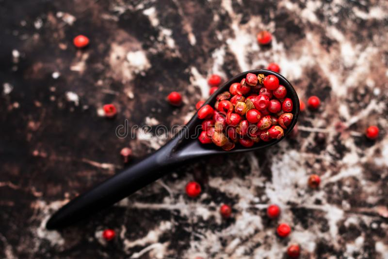 Κλείστε επάνω οργανικά ρόδινα peppercorns ή το ρόδινο μούρο μαύρο σε κεραμικό στοκ εικόνες