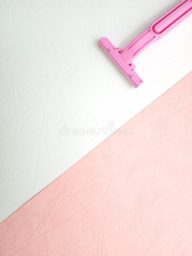 Κλείστε επάνω οριζόντια βάζει τη ρόδινη ξυριστική μηχανή γυναικών στο ρόδινο και άσπρο υπόβαθρο στοκ εικόνες με δικαίωμα ελεύθερης χρήσης