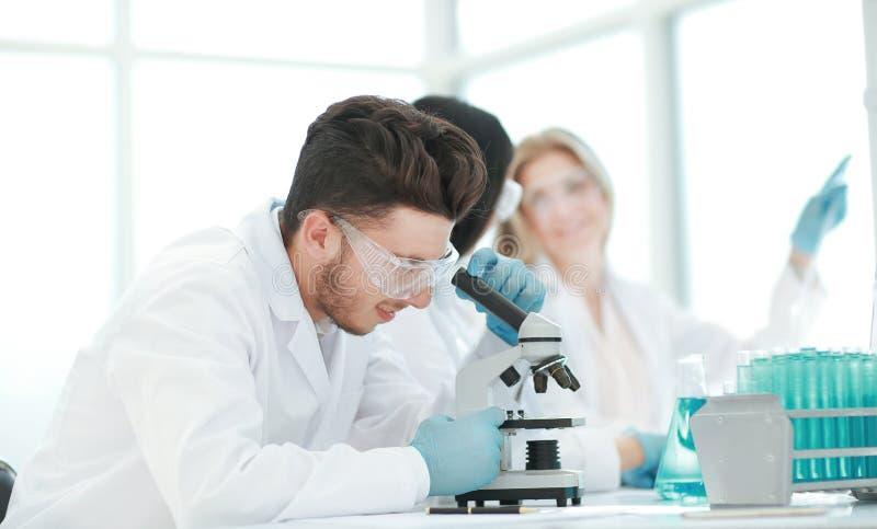 κλείστε επάνω ο αρσενικός επιστήμονας χρησιμοποιεί ένα μικροσκόπιο στο εργαστήριο στοκ φωτογραφία με δικαίωμα ελεύθερης χρήσης