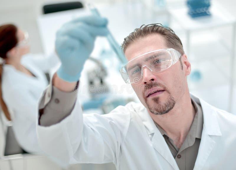 κλείστε επάνω ο χαμογελώντας επιστήμονας εξετάζει το σωλήνα με το υγρό στοκ φωτογραφίες