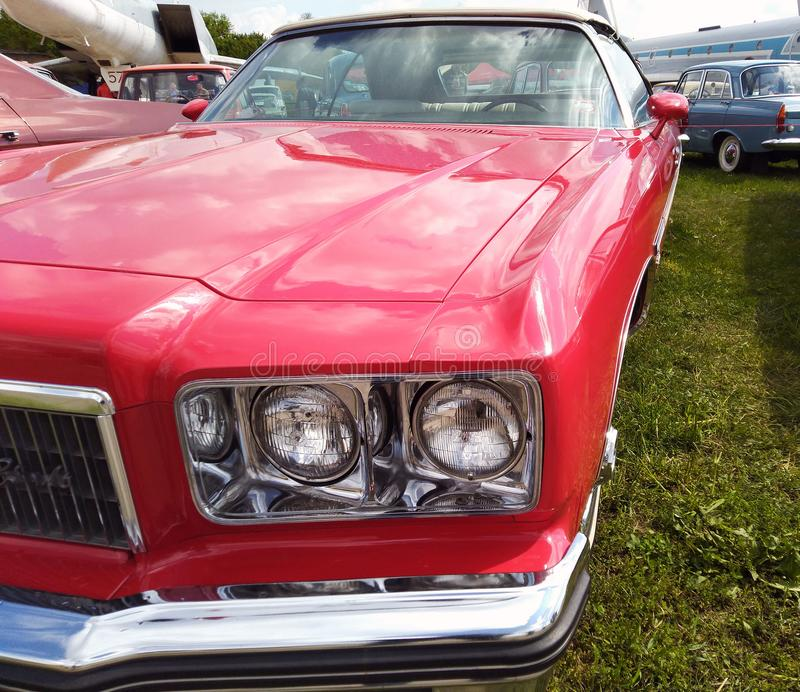 Κλείστε επάνω, προβολείς ενός λαμπρού κόκκινου κλασικού αυτοκινήτου με την εστίαση στους προβολείς και κουκούλα στοκ φωτογραφίες