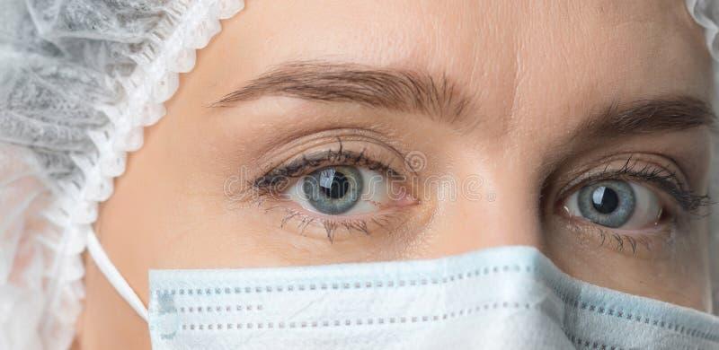 Κλείστε επάνω τα ευρέως ανοιγμένα μάτια του γιατρού Θηλυκός γιατρός στο protecti στοκ φωτογραφία