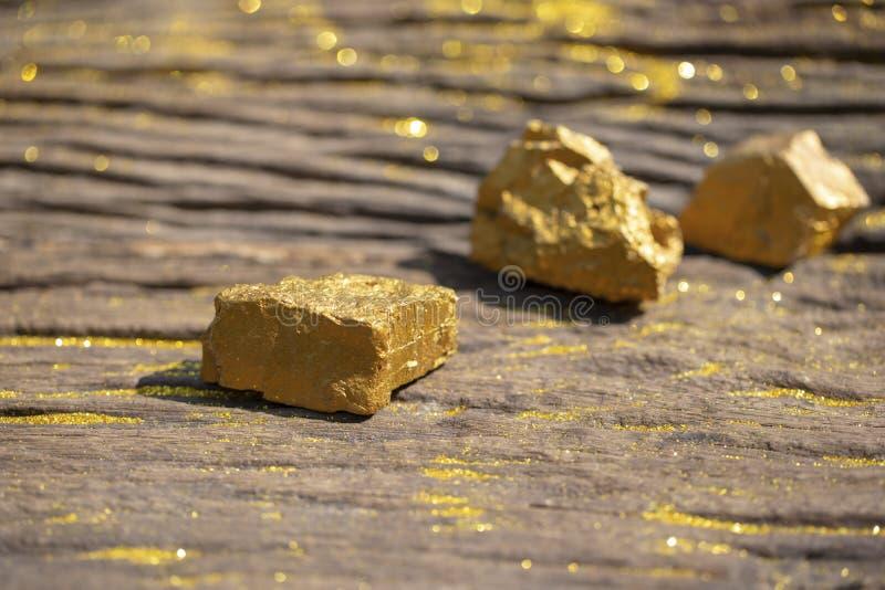 Κλείστε επάνω τα καθαρά χρυσά μεταλλεύματα με το χρυσό φως στην παλαιά πλάτη wooder στοκ εικόνα