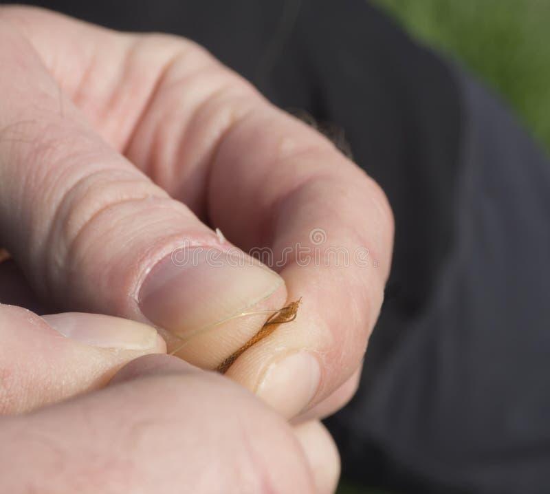 Κλείστε επάνω τα μακρο χέρια ατόμων εστιάζοντας στο εμπλεγμένο τέλος γραμμών αλιείας για την αλιεία στοκ φωτογραφία
