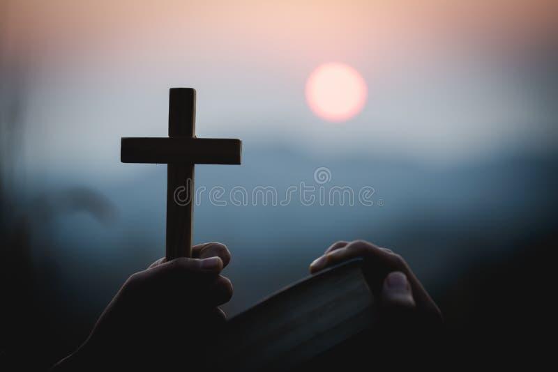 Κλείστε επάνω τα νέα χέρια κρατώντας τον ξύλινο σταυρό πέρα από την ιερή Βίβλο και την επίκληση Χριστιανική έννοια στοκ εικόνα