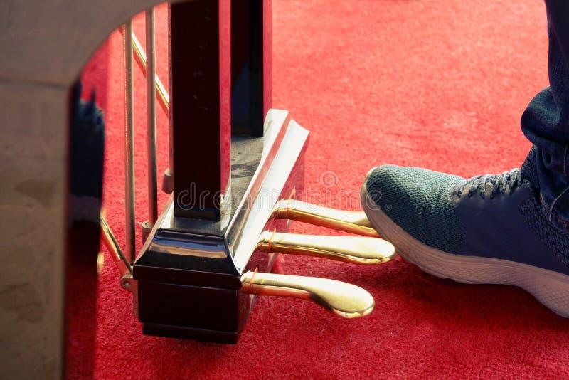 Κλείστε επάνω τα πόδια νεαρών άνδρων παίζοντας στα πεντάλια πιάνων στοκ φωτογραφία με δικαίωμα ελεύθερης χρήσης