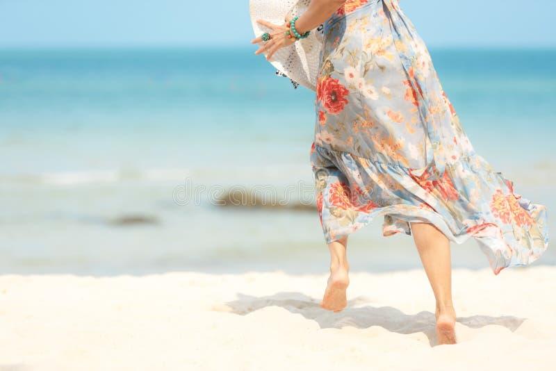 Κλείστε επάνω τα πόδια χαμογελώντας τη γυναίκα τρόπου ζωής που φορά το καλοκαίρι φορεμάτων μόδας που τρέχει στην αμμώδη ωκεάνια π στοκ φωτογραφία