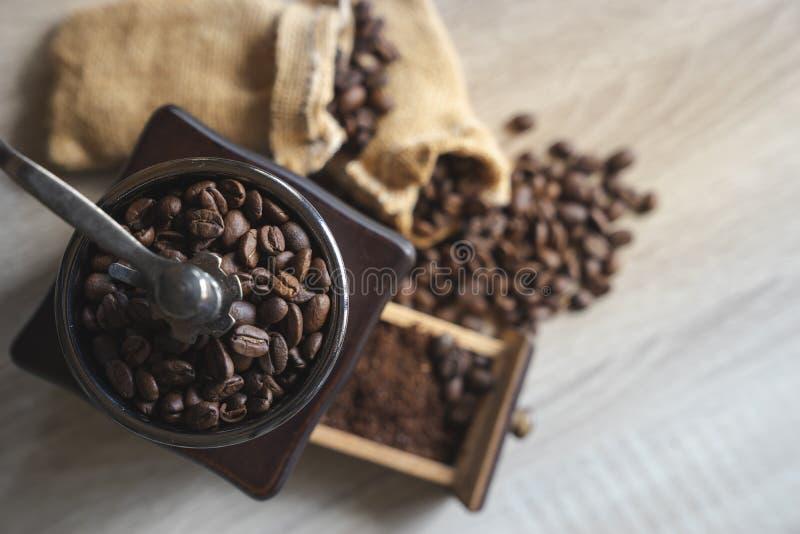 Κλείστε επάνω τα τοπ ψημένα άποψη φασόλια καφέ στον ξύλινο μύλο καφέ στοκ εικόνες με δικαίωμα ελεύθερης χρήσης