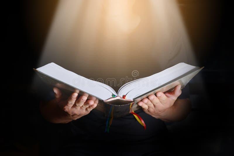 Κλείστε επάνω τα χέρια ατόμων στη Βίβλο στο σκοτάδι Το φως λάμπει κάτω στο θόριο στοκ φωτογραφίες