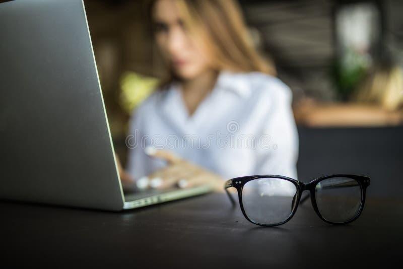 Κλείστε επάνω τα χέρια γυναικών χρησιμοποιώντας το lap-top για την εργασία της για το υπόβαθρο φωτός του ήλιου στο γραφείο στοκ εικόνες