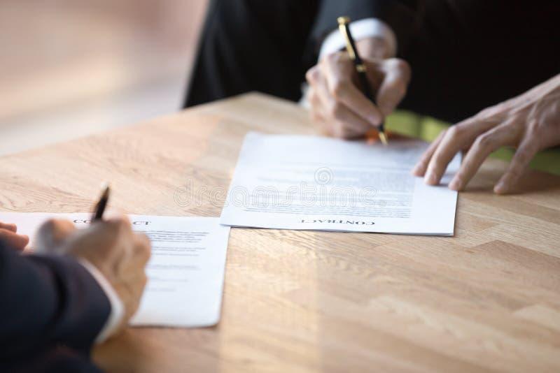 Κλείστε επάνω τα χέρια επιχειρηματιών κρατά τις μάνδρες υπογράφοντας τη σύμβαση στοκ φωτογραφίες με δικαίωμα ελεύθερης χρήσης