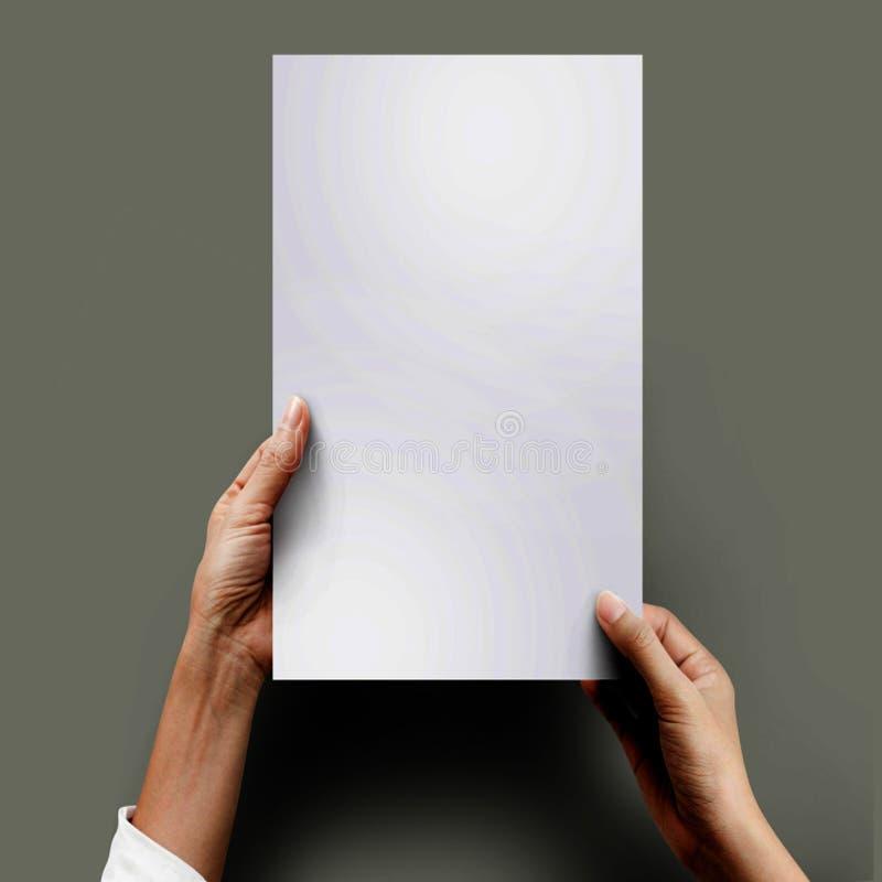 Κλείστε επάνω τα χέρια κρατώντας το κενό έγγραφο για την εργασία στη τοπ άποψη γραφείων γραφείων ψαλιδίζοντας πορεία, γκρι που απ στοκ εικόνες