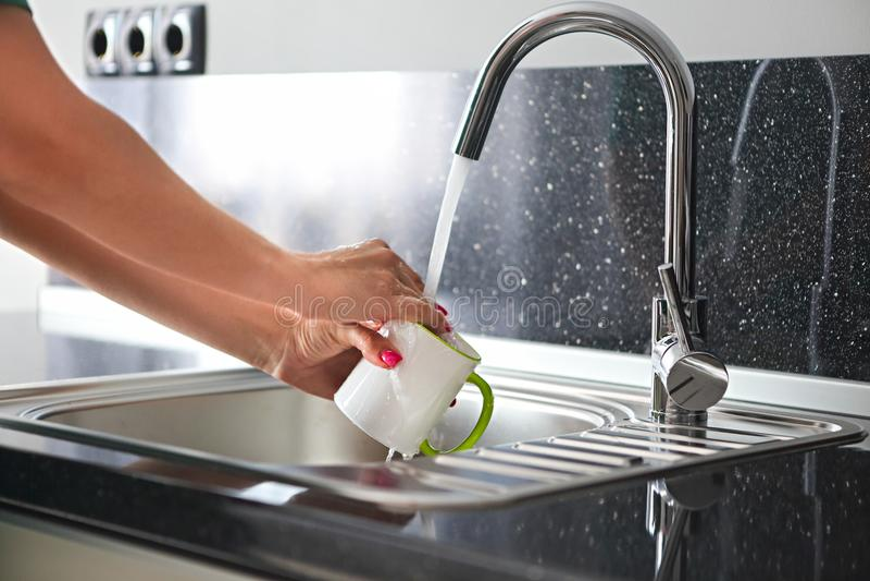 Κλείστε επάνω τα χέρια των πιάτων πλύσης γυναικών στοκ εικόνα