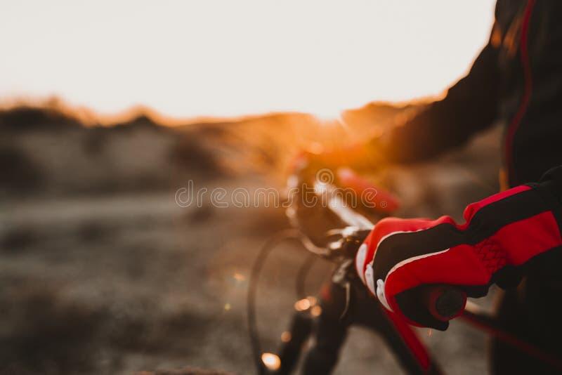 Κλείστε επάνω την άποψη ενός γαντιού και handlebar εξοπλισμού ποδηλατών Άτομο που οδηγά το ποδήλατο κάτω από το δύσκολο Hill στο  στοκ φωτογραφία