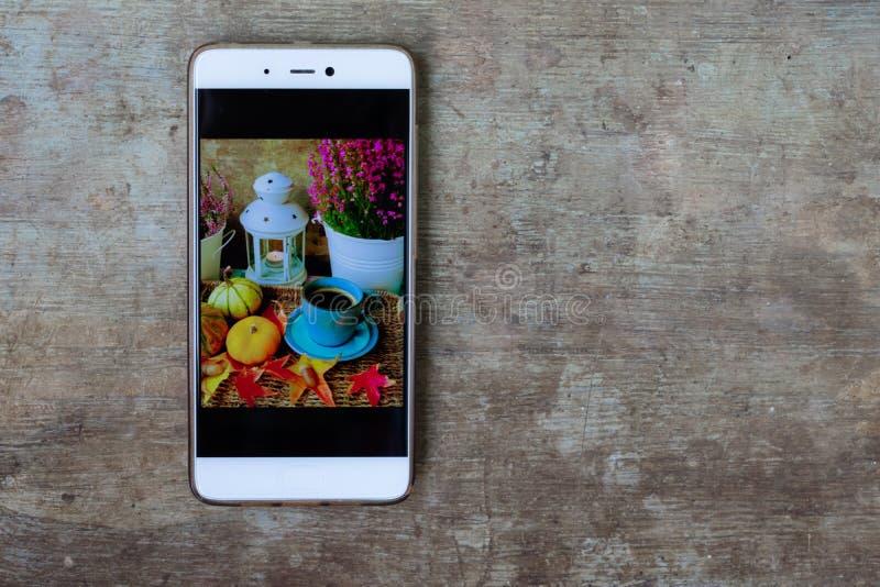 Κλείστε επάνω την άποψη ενός κινητού τηλεφώνου με μια φωτογραφία οθόνης υποβάθρου φθινοπώρου στο παλαιό αγροτικό ξύλινο υπόβαθρο στοκ φωτογραφία