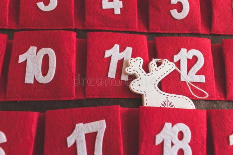 Κλείστε επάνω την άποψη ενός κόκκινου και καφετιού υφαντικού ημερολογίου εμφάνισης με τις ημερομηνίες και μιας διακόσμησης ελαφιώ στοκ φωτογραφία με δικαίωμα ελεύθερης χρήσης
