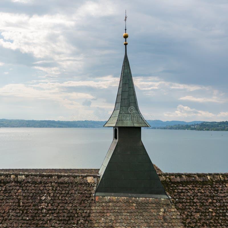 Κλείστε επάνω την άποψη μιας στέγης εκκλησιών με το καμπαναριό και μια άποψη λιμνών πίσω στοκ εικόνες