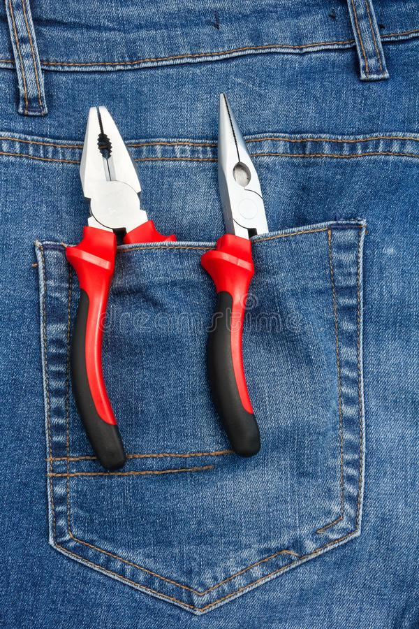 Κλείστε επάνω την άποψη στα εργαλεία εργασίας που κολλούν έξω από μια τσέπη τζιν παντελόνι στοκ εικόνες