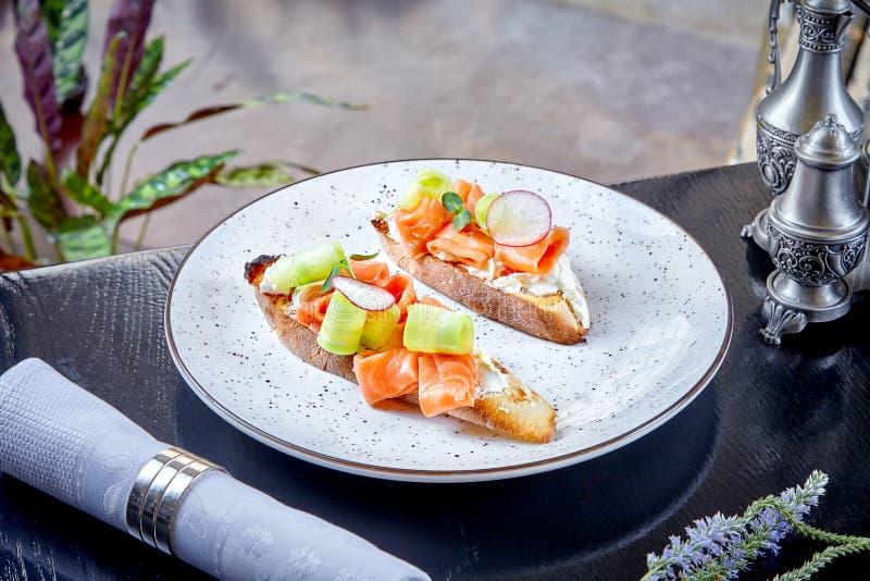 Κλείστε επάνω την άποψη σχετικά με το ciabatta με το τυρί σολομών και κρέμας που εξυπηρετείται στο άσπρο πιάτο r Πρόχειρο φαγητό  στοκ εικόνες με δικαίωμα ελεύθερης χρήσης