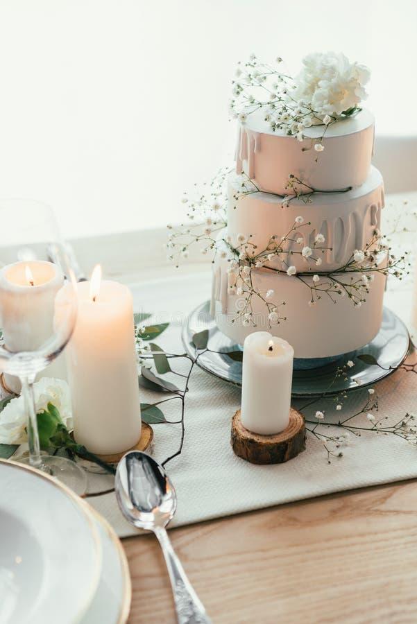 κλείστε επάνω την άποψη του μοντέρνου πίνακα που θέτει με τα κεριά και το γαμήλιο κέικ στοκ φωτογραφίες με δικαίωμα ελεύθερης χρήσης