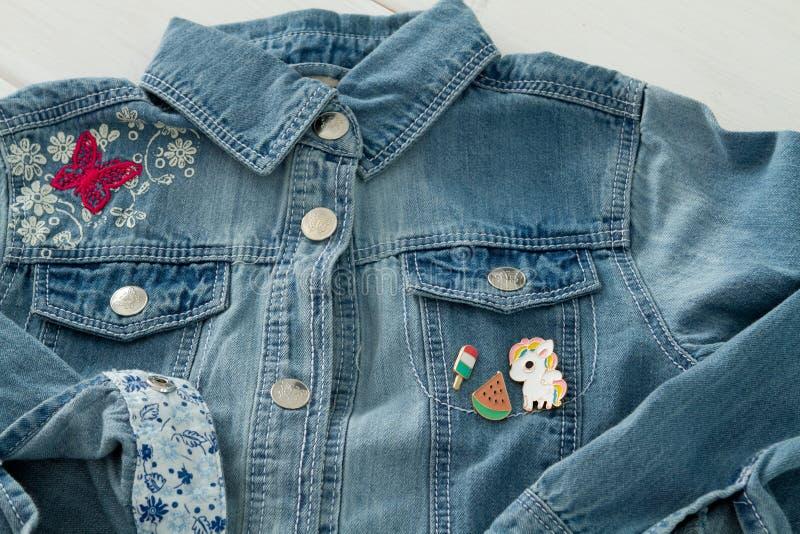 Κλείστε επάνω την άποψη του σακακιού τζιν τζιν με τις δροσερές γραφικές καρφίτσες στοκ εικόνες με δικαίωμα ελεύθερης χρήσης