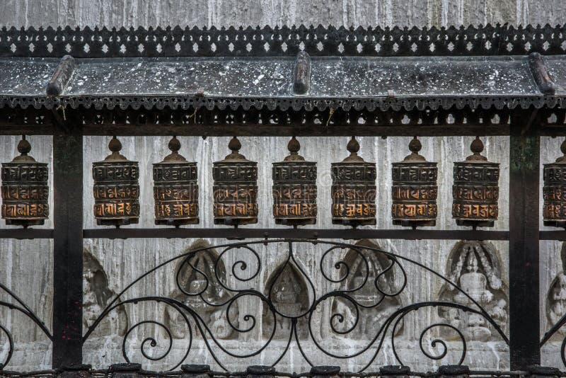 Κλείστε επάνω την άποψη του φράκτη μετάλλων με δωδεκάια βουδιστική ρόδα προσευχής στοκ εικόνες