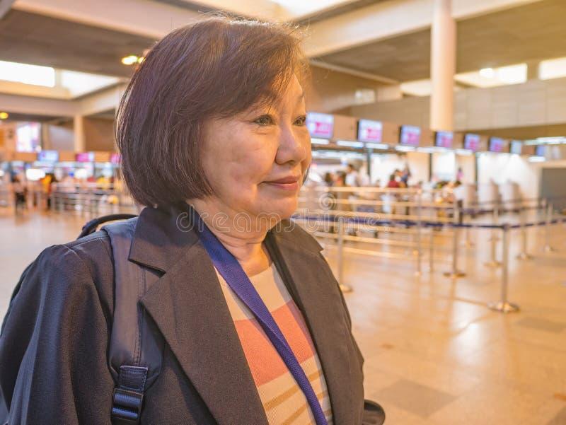 Κλείστε επάνω την ανώτερη ασιατική γυναίκα φορά μέσα muang το διεθνή αερολιμένα Μπανγκόκ στοκ φωτογραφίες